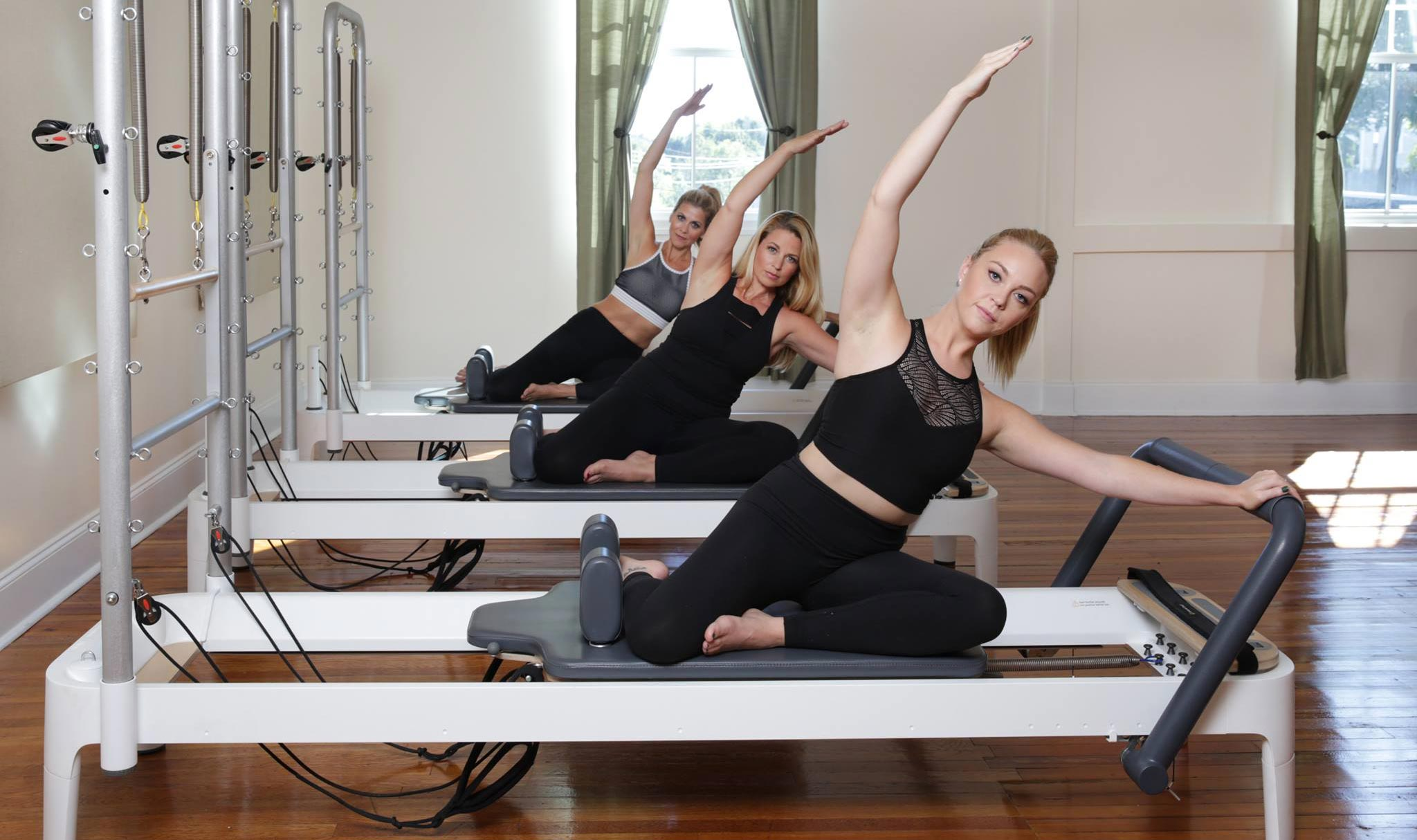 Photo of three Precision Pilates instructors on reformers