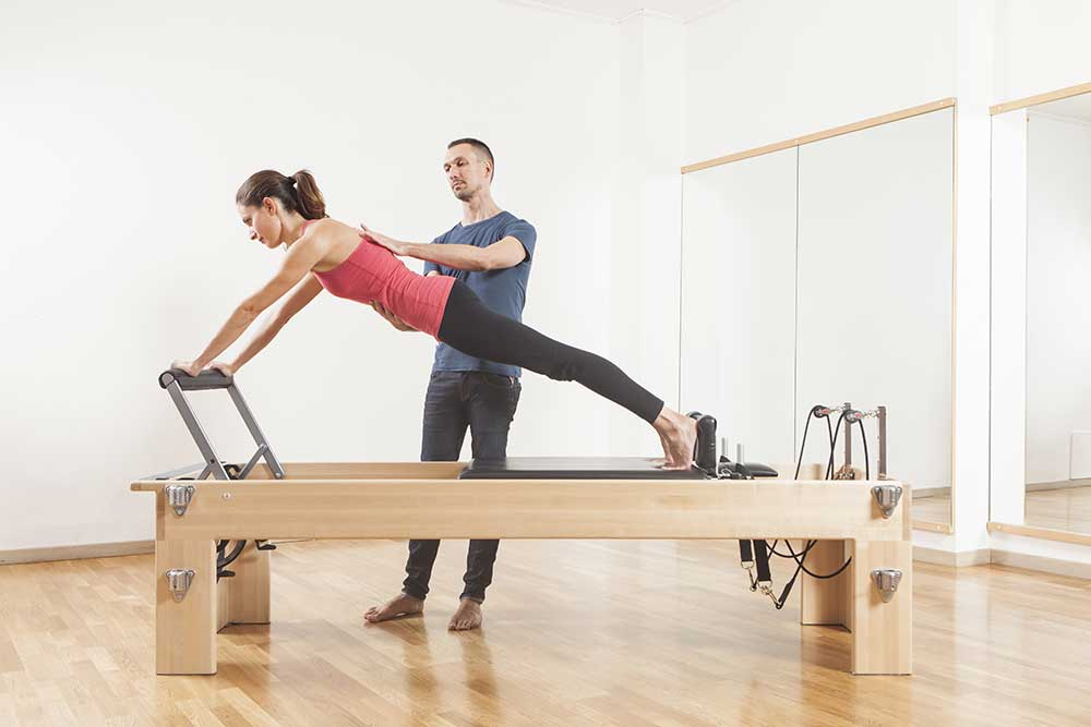 Photo of instructor with student holding plank pose on reformer