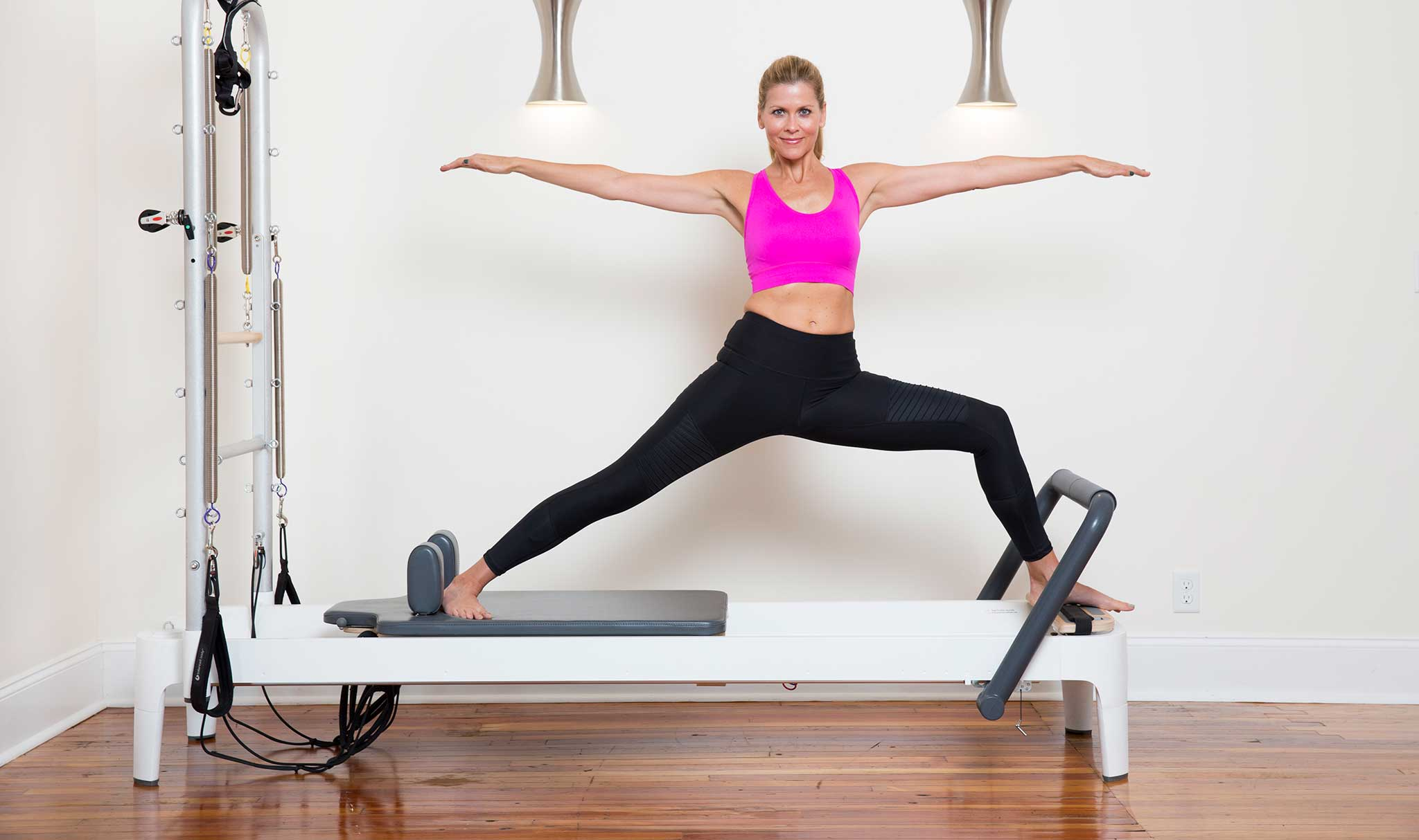 Giglia in warrior one pose on reformer